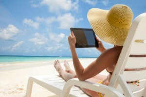 Woman holding tablet computer sitting on the beach in deck chair and taking sun bath
